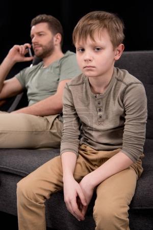 Foto de Malestar pequeño hijo sentado en el sofá mientras padre hablando en teléfono inteligente detrás, concepto de problemas familiares - Imagen libre de derechos