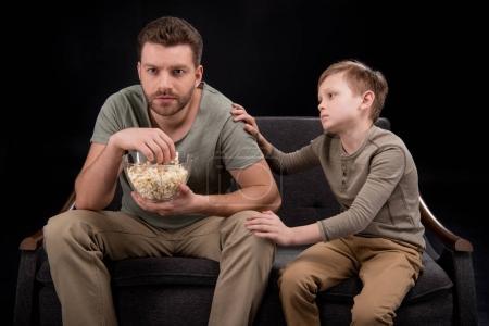 Foto de Niño tratando de hablar con padre comiendo palomitas y viendo la tv en el sofá, concepto de problemas familiares - Imagen libre de derechos