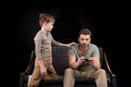 Photo for Boy trying to talk with father playing with joystick, family problems concept - Royalty Free Image