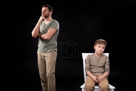 Photo pour Le père debout, main sur menton et bouleversé petit garçon assis sur le tabouret, notion de problèmes familiaux - image libre de droit