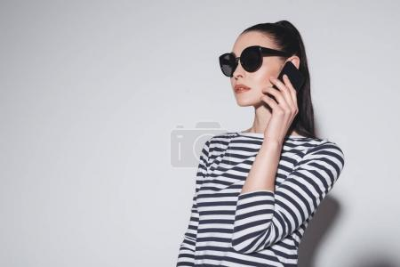 Photo for Gorgeous stylish young woman in sunglasses talking on smartphone isolated on grey - Royalty Free Image