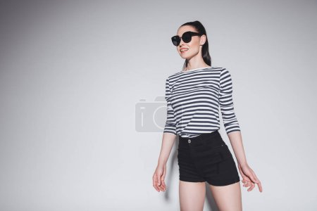Photo for Gorgeous brunette girl in sunglasses smiling and looking away isolated on grey - Royalty Free Image