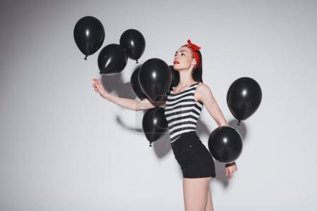Stylish woman with black balloons