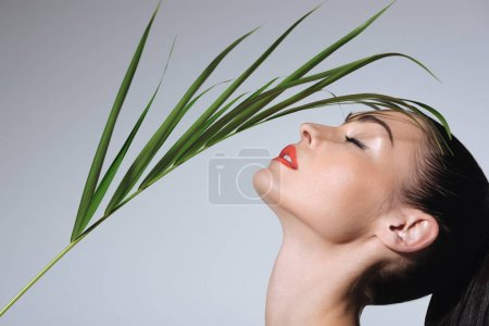 Photo for Close-up view of beautiful young woman with perfect skin holding green palm leaf - Royalty Free Image