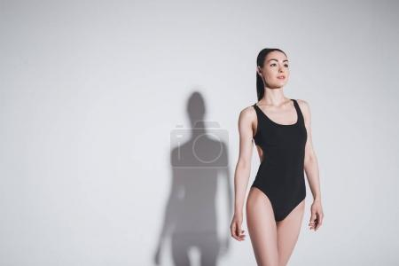 Photo for Beautiful brunette woman in black stylish bodysuit smiling and looking away in studio - Royalty Free Image