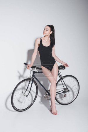 Photo for Gorgeous young brunette woman in stylish leotard posing with bicycle on grey - Royalty Free Image