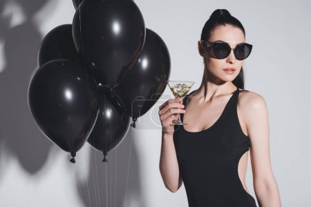 Photo for Gorgeous young woman in sunglasses and swimsuit drinking martini while standing in studio with black balloons - Royalty Free Image