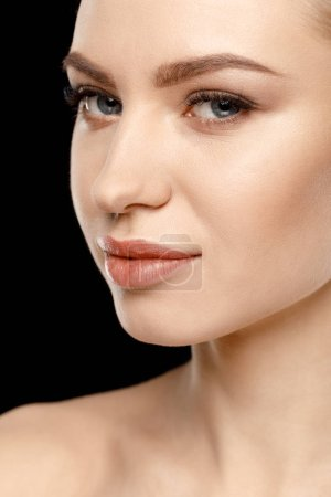 Photo pour Close-up portrait of gorgeous young woman smiling at camera isolated on black - image libre de droit