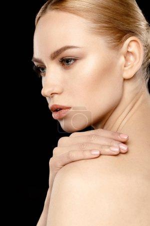 Photo pour Magnifique jeune femme avec la main sur l'épaule regardant loin isolé sur noir - image libre de droit