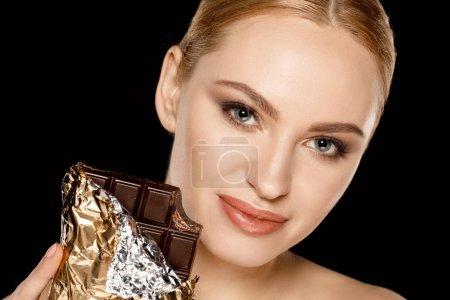 Photo pour Portrait de femme souriante avec barre de chocolat isolé sur noir - image libre de droit