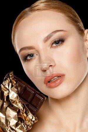 Photo pour Femme avec barre de chocolat isolé sur noir regardant à la caméra - image libre de droit