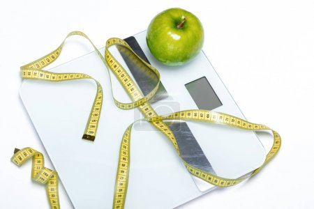 Photo for Close-up view of digital scales with green apple and measuring tape  isolated on white - Royalty Free Image