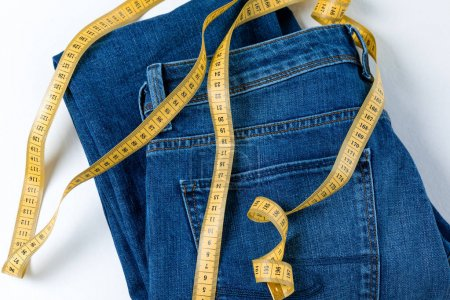 Photo for Close-up view of oversized pair of jeans and measuring tape isolated on white - Royalty Free Image