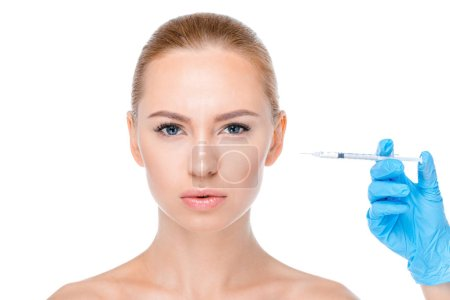 Photo pour Portrait of serious woman getting botox injection isolated on white - image libre de droit
