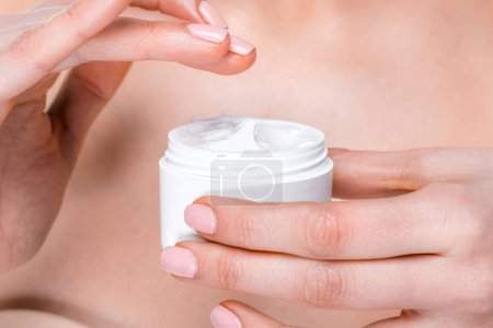 woman showing face cream