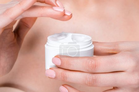 Foto de Partial close up view of female hands holding face cream isolated on white - Imagen libre de derechos