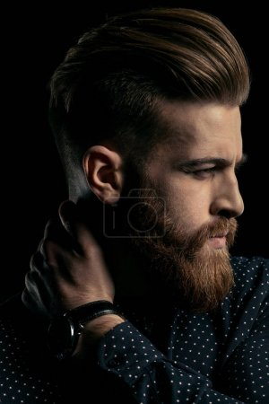 Photo for Close-up portrait of handsome stylish bearded man with hand on neck - Royalty Free Image