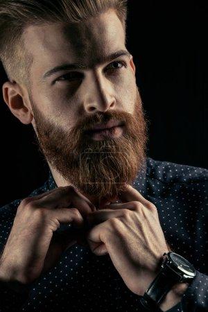 Foto de Retrato de primer plano de hipster hombre guapo con barba abotonarse la camisa - Imagen libre de derechos