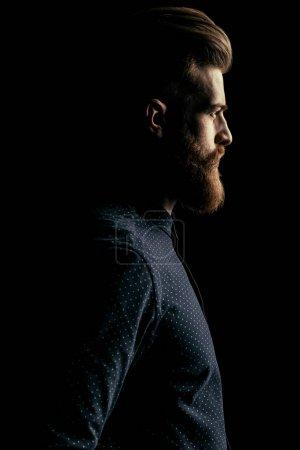Foto de Vista lateral de serio guapo barba hombre mirando lejos en negro - Imagen libre de derechos