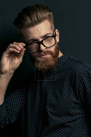 Photo for Handsome bearded young man hipster adjusting eyeglasses and looking at camera - Royalty Free Image