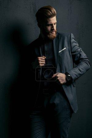 Photo pour Élégant beau barbu homme en costume tendance posant sur fond noir - image libre de droit
