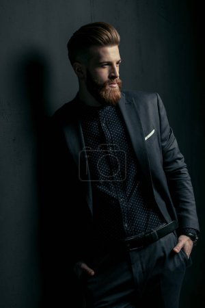 Photo for Stylish handsome bearded man in trendy suit standing with hands in pockets on black - Royalty Free Image