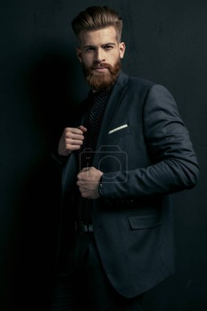 Photo for Stylish handsome bearded man in trendy suit posing on black - Royalty Free Image