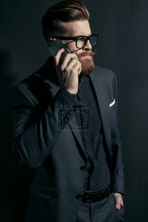 Photo for Handsome bearded businessman in stylish suit and eyeglasses talking on smartphone on black - Royalty Free Image