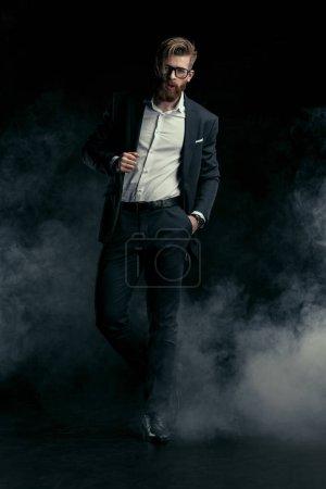 Foto de Elegante hombre barbudo guapo en traje de moda y gafas graduadas posando en el humo - Imagen libre de derechos