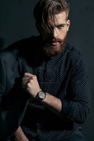 Photo for Stylish handsome bearded man hipster with jacket on shoulder looking at camera - Royalty Free Image