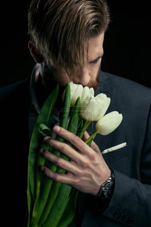 Photo for Stylish businessman in suit holding tulips on black, mother's day holiday concept - Royalty Free Image