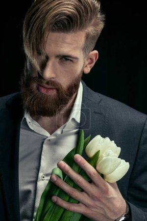 Photo for Portrait of stylish man in suit holding tulips on black, mother's day holiday concept - Royalty Free Image