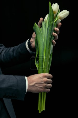 Photo for Partial view of man holding tulips in hands on black, international women's day concept - Royalty Free Image
