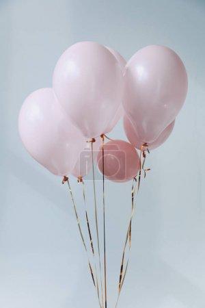 Photo pour Ballons à air rose avec rubans dorés isolés sur gris - image libre de droit