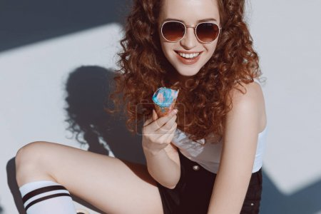 Foto de Hermosa chica de pelo rojo en gafas de sol comiendo helado, chica hipster sonriendo - Imagen libre de derechos