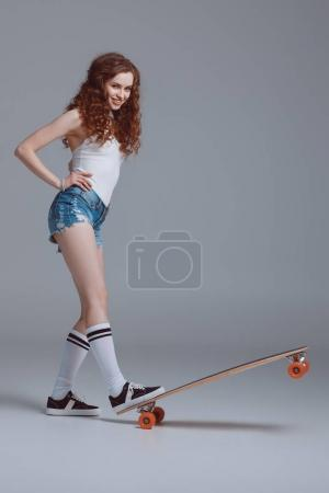 Stylish young woman with skateboard