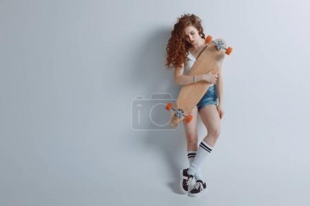 Photo for Young stylish hipster girl posing with skateboard isolated on grey - Royalty Free Image