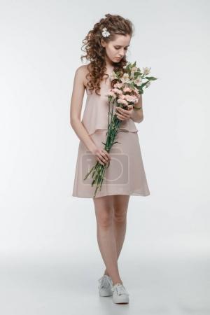 Foto de Atractiva joven con ramo de flores de primavera aislado en blanco - Imagen libre de derechos