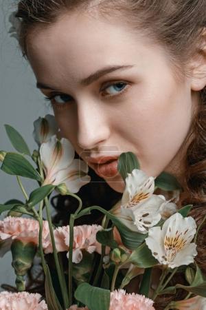Foto de Retrato de mujer joven atractiva con ramo de flores de primavera aislado en gris - Imagen libre de derechos