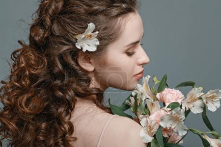 Foto de Vista posterior de mujer joven atractiva con ramo de flores de primavera aislado en gris - Imagen libre de derechos