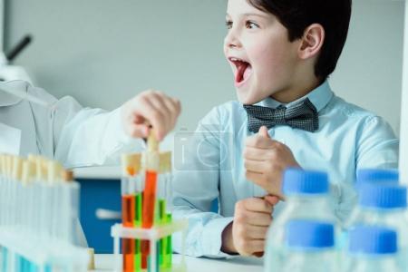 Photo pour Écolier excité avec des flacons en laboratoire chimique, concept de l'école de sciences - image libre de droit