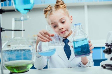 Photo pour Écolière en blouse blanche faisant expérience avec les réactifs de laboratoire - image libre de droit