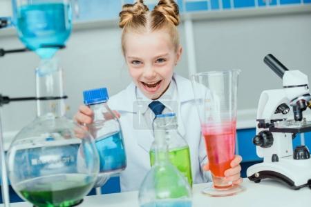Photo pour Écolière en manteau blanc faisant l'expérience avec des réactifs dans le laboratoire de science - image libre de droit