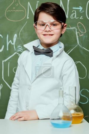 Boy in lab coat and protective glasses