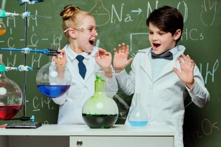 Photo for Little kids in white coats with chalkboard behind in laboratory, scientists kids team concept - Royalty Free Image