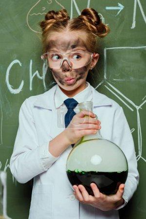 Photo pour Portrait de fille en blouse blanche tenant le ballon avec tableau noir derrière au laboratoire des sciences - image libre de droit