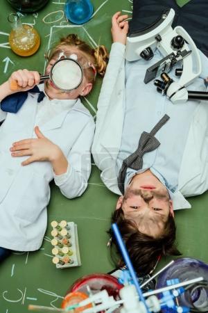 kids in lab coats lying on chalkboard