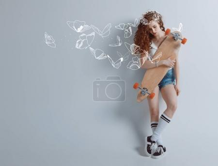 Photo for Young hipster redhead girl with drawn butterflies holding longboard - Royalty Free Image