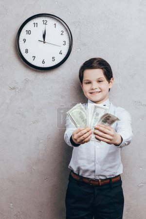 Smiling child showing money