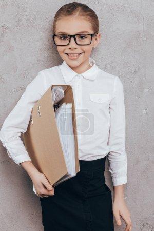 Photo pour Portrait d'une fillette souriante avec dossier en main en regardant caméra isolée sur fond gris - image libre de droit